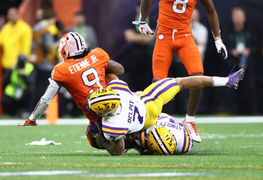 LSU Tigers safety Grant Delpit (7) tackles Clemson Tigers running back Travis Etienne (9) in the College Football Playoff national championship game.