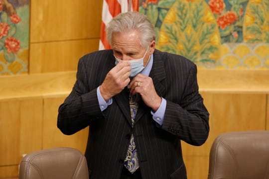 State Sen. Jim Nielsen, R-Gerber, vice chair of senate budget committee, puts on a face mask before the start of a hearing of the special subcommittee on COVID-19, at the Capitol in Sacramento, Calif., Thursday, April 16, 2020. Lawmakers are looking into how Gov. Gavin Newsom has been spending money to address the new coronavirus crisis. Following social distancing procedures, only Nielsen and Sen. Holly Mitchell, D-Los Angeles, chair of the budget committee, attended the hearing in person while other committee members joined by video.