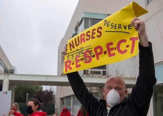 A husband of one of the nurses holds a sign to show his support during the statewide vigil on Thursday, April 16, 2020.