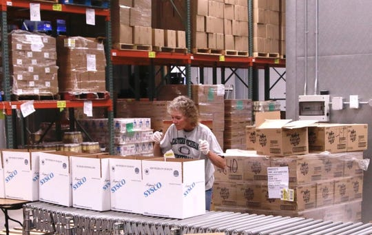 Lynelle Asher packs boxes with food at the Feeding South Dakota distribution center in Pierre on April 7. She said volunteering is a way to fight back against COVID-19 and help people who are struggling to make ends meet during the pandemic.