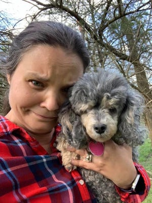 Amanda Harlan Mendenhall holds Cricket, her blind and deaf poodle, moments after finding the dog in the woods nearly two miles from home.
