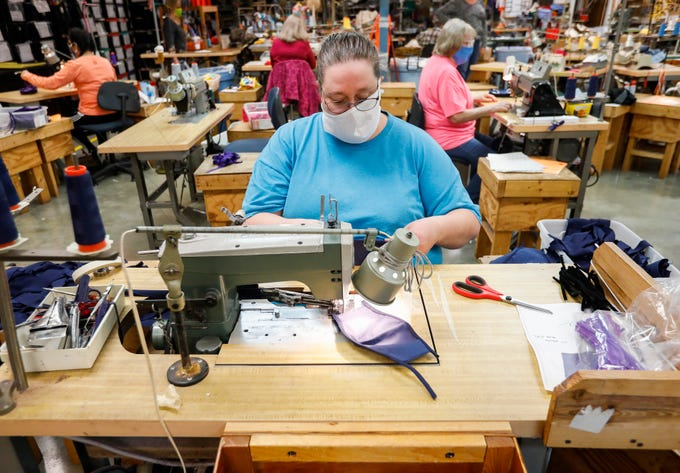 Felicia Black sews together a face mask at Third Street Sportswear in Ozark, Mo., on Friday, April 17, 2020.
