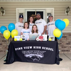 Pine View senior Kaitlin Roundy poses with her family as she signs her letter of intent to play at Lakes Community College.