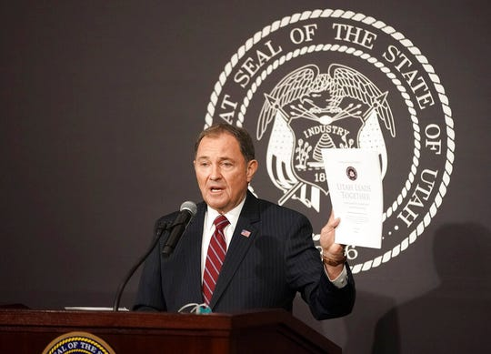 """Utah Gov. Gary Herbert holds up the """"Utah Leads Together Plan"""" while speaking during a press conference with legislative, community, and business leaders at the Utah State Capitol Friday, April 17, 2020, in the Salt Lake City. Utah is aiming to reopen restaurants and gyms and resume elective surgeries in early May under a plan to gradually reopen the economy that has been decimated by the coronavirus pandemic, Gov. Herbert said Friday. (Jeffrey D. Allred/Deseret News, via AP, Pool)"""