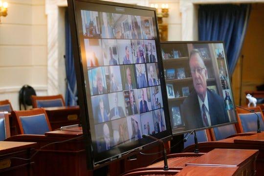Senators are shown on video monitors in a nearly empty Senate chambers during the Utah Legislature's virtual special session at the Utah State Capitol Thursday, April 16, 2020, in Salt Lake City. (AP Photo/Rick Bowmer)