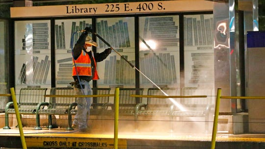 Utah Transit Authority personnel clean and disinfect a train station to prevent the spread of the coronavirus virus Friday, April 17, 2020, in Salt Lake City. Crews are sent out daily to clean and disinfect all rail stations, including all surfaces that are frequently touched.  (AP Photo/Rick Bowmer)