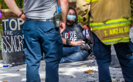 Protester Jordan Mazurek, 28, who cemented his hands in two 55-gallon plastic drums in the driveway of the Governor's Mansion, sits on the pavement while his vitals are checked by first responders, Friday, April 17, 2020. Mazurek is protesting how Gov. Ron DeSantis is handling coronavirus in state prisons.