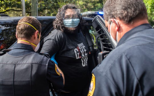 Protester Jordan Mazurek, 28, who cemented his hands in two 55-gallon plastic drums in the driveway of the Governor's Mansion, being escorted in handcuffs to a TPD car, Friday, April 17, 2020. Mazurek is protesting how Gov. Ron DeSantis is handling coronavirus in state prisons.