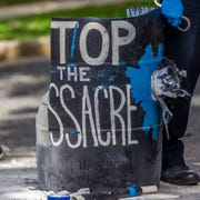 "One of two 55-gallon plastic drums that were used by protester Jordan Mazurek, who cemented his hands inside the barrels in the driveway of the Governor's Mansion, was painted with the words ""stop the massacre,"" Friday, April 17, 2020. Mazurek is protesting how Gov. Ron DeSantis is handling coronavirus in state prisons."