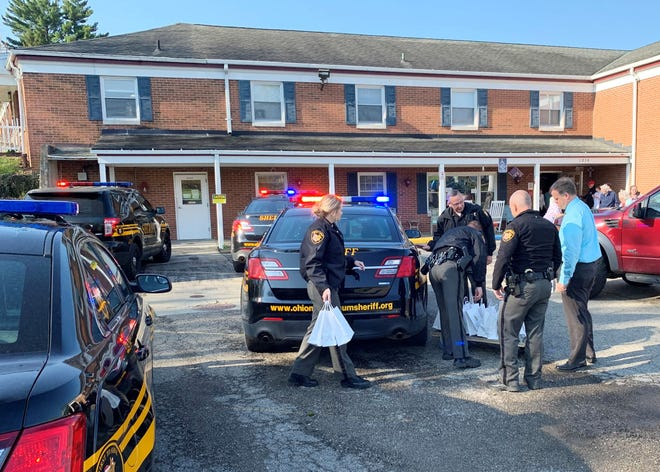 Deputies and officials from the Muskingum County Sheriff's Office arrive at Abbot Senior Living in Zanesville with treat bags for senior residents and staff.