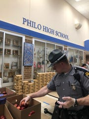 Trooper Scott Leach of the Zanesville patrol post works to fill school lunch bags at Philo High School this week. Trooper Leach was one of more than 40 volunteers preparing 2,500 bags of food for Franklin Local School students.