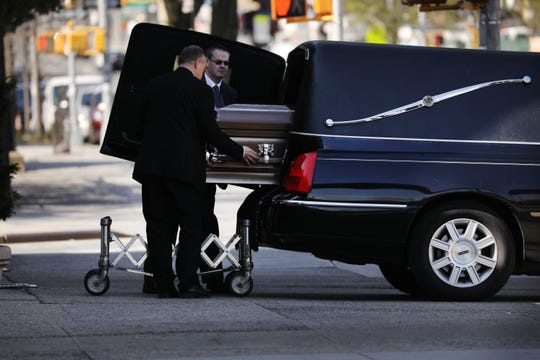 A casket is placed into a hearse outside a funeral home in the heavily Orthodox Borough Park neighborhood of Brooklyn in New York City, which has seen a large number of deaths from the coronavirus.