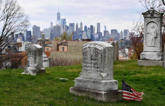 In this file photo taken on April 10, 2020, the skyline of lower Manhattan with One World Trade Center is seen from a Green-Wood Cemetery in New York City.  Brooklyn's Green-Wood cemetery has seen cremations more than double and five times more burials than usual, as coronavirus claims the lives of New Yorkers by the thousands. The city's largest cemetery -- beloved for its meandering hills, glacial ponds and vibrant flora -- began preparing for an influx years ago, during the 2013-2016 Ebola epidemic that ultimately left the United States largely unscathed.