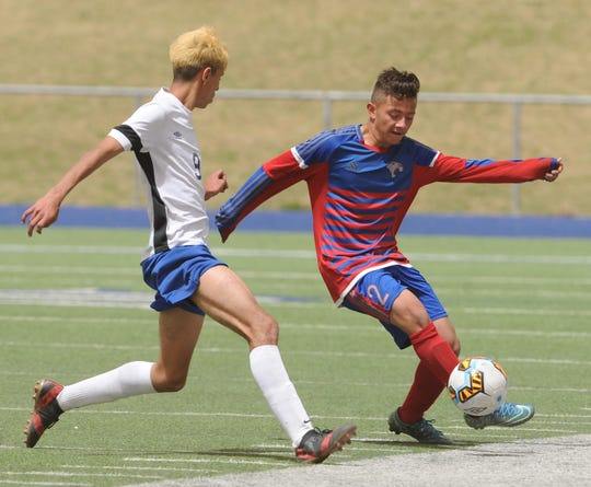 Cooper's Jose Ortega, right, plays the ball as El Paso Bowie's Raul Nieto Esparza defends. Bowie beat the Cougars 2-0 in the Region I-5A area playoff game April 3, 2018, in Midland.