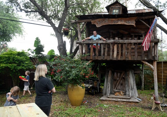 Jason Barnes, top right, sits in his kids' treehouse while his family plays in their backyard, Saturday, April 18, 2020. Jenna Barnes, second from left, teaches their children the importance of social distancing and why their dad must self-quarantine in the backyard.