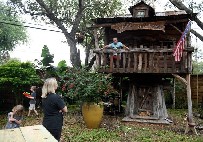 Jason Barnes, top right, sits in his kids' treehouse while his family plays in their backyard April 18, 2020.