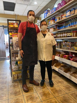 Elias Bitar and his mother, Norma Bitar, stand in masks in their family's grocery store, attached to Norma's restaurant in Cherry Hill. The family has run the Middle Eastern restaurant market for more than 25 years.