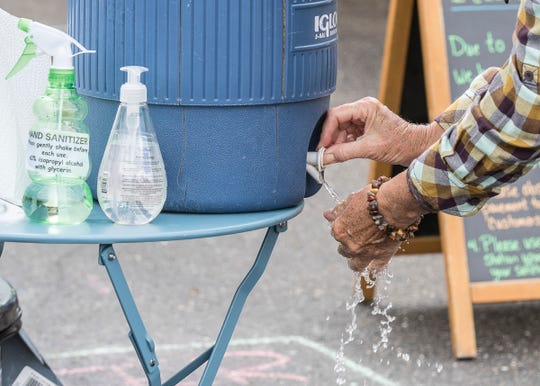 Hand wash stations are set up at the entrance and exit of the winter's market to try and fight the coronavirus spread on April 18, 2020.