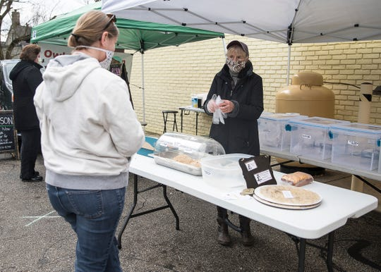 Sharon Williamson from Owl Creek Artisan Breads changes gloves in between every transaction to try and stay as sanitary as possibly at Chillicothe's winter market on April 18, 2020.