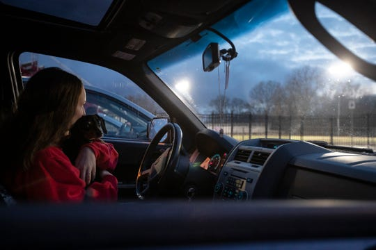Jenna Bleser, a Lakeshore High School senior, sits in the car with her dog Lucy, as she watches the lights of the football stadium being turned on at St. Clair Shores Lake Shore High School on April 17.