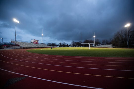 Will Puvalowski, head football coach of Lakeshore High School, walks onto the field as he watches the lights of the football stadium being turned on at St. Clair Shores Lake Shore High School in St. Clair Shores on April 17, 2020. The stadium lights were turned on at 8:20 pm for 20 minutes and 20 seconds to honor the Class of 2020.