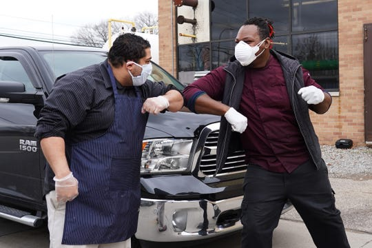 Saffron De Twah owner and chef Omari Anani (left) and YumVillage owner and chef Godwin Ihentuge greet each other while dropping off food for workers at Beaumont Hospital, Wayne on April 13, 2020 as part of the Rescue Detroit Restaurants / Feed Health Care Heroes program.