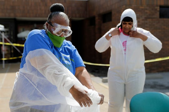 Licensed practical nurse Lenora Shepard, left, removes a protective gown, next to registered medical assistant Lauiesha Plummer after working at a drive-thru COVID-19 testing site Thursday, April 16, 2020, in St. Louis. (AP Photo/Jeff Roberson)