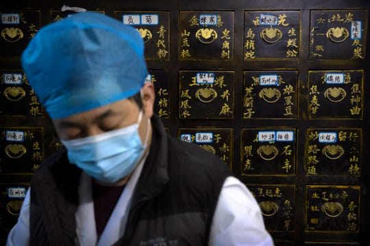 In this March 13, 2020 photo, a worker fills orders for prescriptions in front of a cabinet of drawers containing ingredients for traditional Chinese medicine preparations at the Bo Ai Tang traditional Chinese medicine clinic in Beijing.