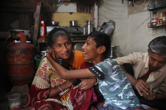 In this March 31, 2020, photo, Mina Ramesh Jakhawadiya, left, shares light moment with her son Ritik Ramesh in her one room house in a slum in Mumbai, India. Jakhawadiya makes a living selling cheap plastic goods with her husband on the streets of Mumbai.