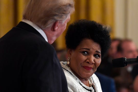 President Donald Trump, left, listens as former prisoner Alice Marie Johnson speaks April 1, 2019, at the 2019 Prison Reform Summit and First Step Act Celebration in the East Room of the White House in Washington.