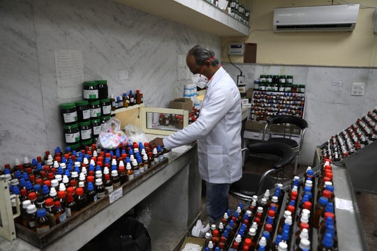 In this Thursday, March 12, 2020, photo, a doctor makes homeopathic pills in New Delhi, India. With no approved drugs for COVID-19, some people are turning to alternative medicines without evidence that they work.