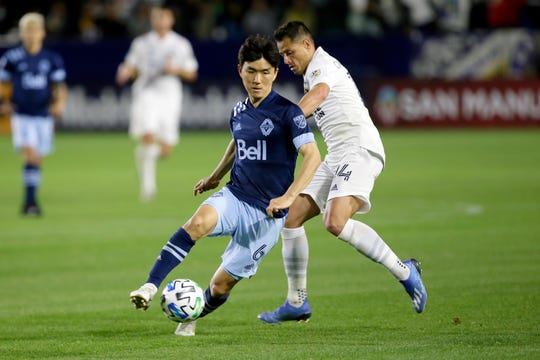 Vancouver Whitecaps midfielder Hwang In-Beom, left, controls the ball away from LA Galaxy forward Javier Hernandez, right, during a match March 7.
