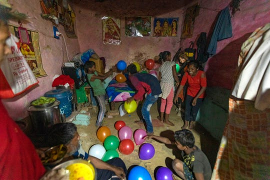In this April 3, 2020, photo, Rajesh Dhaikar's children play with balloons in their house in Prayagraj, India. Dhaikar has a small balloon stall in a nearby market, selling plastic bursts of red and blue and yellow one at a time, and rarely earning more than $2.50 a day. His wife, Suneeta, makes about $20 a month cleaning homes.