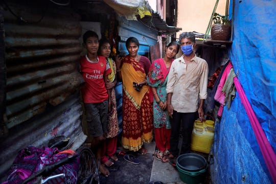 In this April 3, 2020, photo, Mina Ramesh Jakhawadiya, center, poses for a picture with her family members, son, Ritik Ramesh, left, daughters Vaijayanti Ramesh, second left, Guddi Ramesh, second right, and husband Ramesh Karsan Jakhawadiya, outside her one room house in a slum in Mumbai, India. Jakhawadiya makes a living selling cheap plastic goods with her husband on the streets of Mumbai.