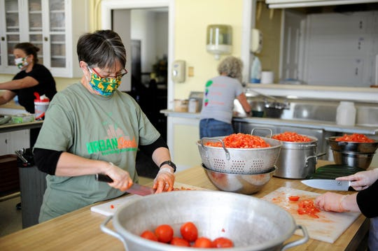 Carla Lemar volunteers with Urban Seeds by chopping tomatoes for a chicken taco salad on Thursday, Apr. 15, 2020.