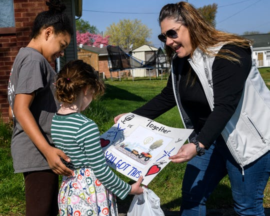 Teri Barnes, from right, presents a keepsake poster to Kynleigh Dalton, 6, as her sister Kyra, 12, looks on after the Caravan for Granted Kids drove by the Dalton family's home in Dale, Ind., Saturday morning, April 18, 2020. Granted, an Evansville-based non-profit that grants wishes to kids with terminal or life-threatening injuries, has caravans scheduled for the next two Saturdays, in which they will visit the rest of the Granted kids.