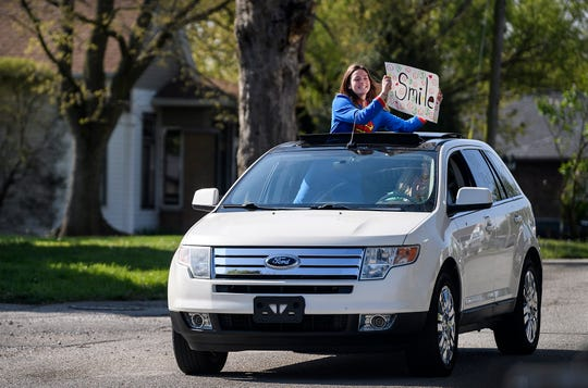Hope Lensing, a Memorial High School junior, hoists a sign out of a sunroof as she says hello to Kynleigh Dalton and her family during the first stop of the Caravan for Granted Kids event in Dale, Ind., Saturday morning, April 18, 2020. Granted, an Evansville-based non-profit that grants wishes to kids with terminal or life-threatening injuries, has caravans scheduled for the next two Saturdays, in which they will visit the rest of the Granted kids.