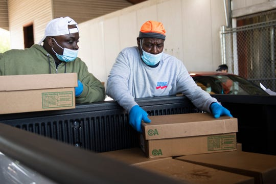 Albert Thompson (right) and Charles Belcher load boxes of chicken into the truck of a customer at the House of Raeford at the Greenville State Farmers Market Saturday, April 18, 2020.