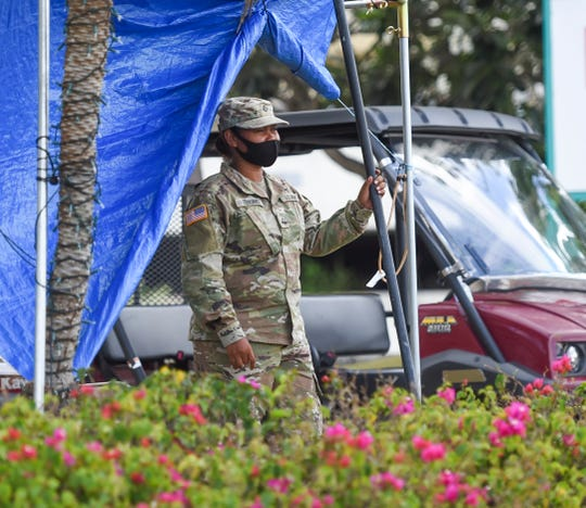 A Guam National Guard soldier questions the driver of an entering vehicle at the Pacific Star Resort & Spa entrance in Tumon, April 18, 2020.
