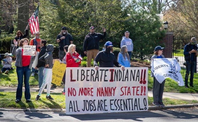 Some of about 250 people who lined both sides of Meridian Street adjacent to the Governor's Residence on Saturday, April 18, 2020 hold signs. The protesters want businesses in Indiana reopened during the coronavirus pandemic.
