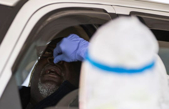 Spencer Johnson gets tested by health professionals with a small swab stuck through his nose at the testing site at the Jackson Fairground in Jackson, Tenn., Saturday, April 18, 2020. Hundreds arrive early before the gates open to get tested for COVID-19.