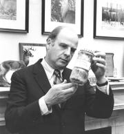Sen. Gaylord Nelson holds a jar of contaminated water from the Potomac River sent to him by a tourist to Washington in 1973.
