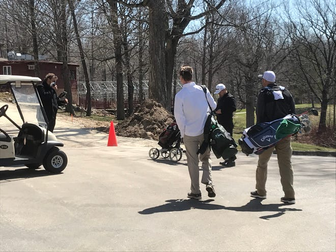 Kettle Hills Golf Course head professional Bryan Fillinger, left, stops golfers before they leave the parking lot to create a proper social distance before teeing off. Washington County golf courses opened Saturday.
