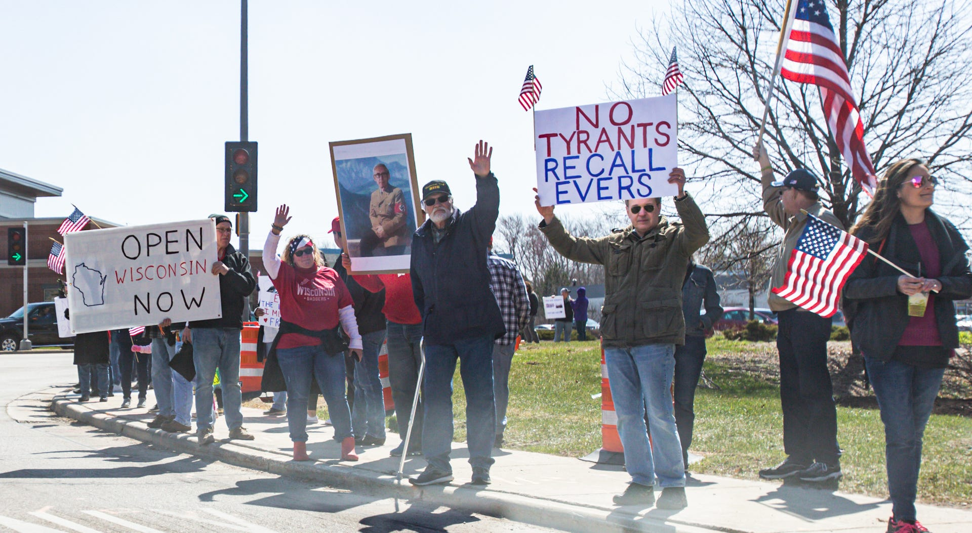 Demonstrators wave flags and hold signs for passing motorists on West Bluemound Rd. in front of Brookfield Square shopping mall on Saturda. The gathering was a protest of Gov. Tony Evers' decision to extend the stay-at-home order through May 26.
