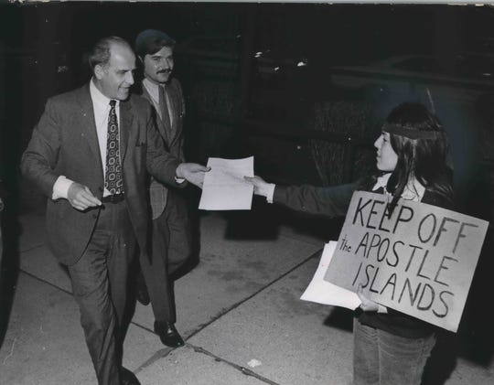 Carmen Ninham,  a member of the  Oneida tribe, hands a pamphlet to U.S. Sen. Gaylord Nelson of Wisconsin as he arrives at Milwaukee Area Technical College to speak at a rally on the first Earth Day in 1970.