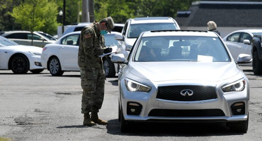 Tennessee National Guard members assess people as they wait in line to be tested for the coronavirus Saturday, April 18, 2020, at the Williamson County Health Department in Franklin, Tenn.