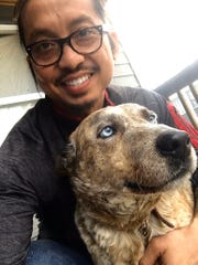 Phom Sisoukrath, 39, poses with Phoenix, a dog he found after the Tuesday, March 3, 2020, tornado destroyed parts of Middle Tennessee.