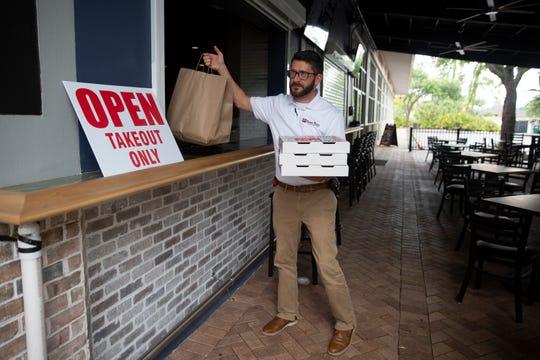 Customer Matt Eberhard picks up his order, Thursday, April 16, 2020, at Seaside Bar and Grill in Bonita Springs.
