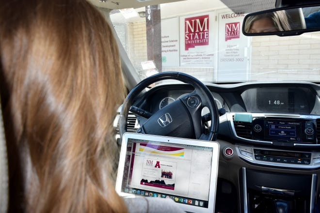 New Mexico State University student Lilly McCarty access her online class while sitting in the parking lot of the Valencia County Extension office. Most of the NMSU Extension county offices have wireless internet available for rural students who have limited access.