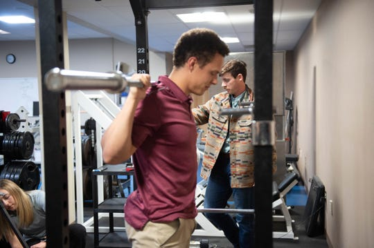 Isaac Halloran, an undergraduate kinesiology student at New Mexico State University, demonstrated the back squat lifting technique used in doctoral student Cameron Munger's research during a photo shoot in early March at Rentfrow Hall.
